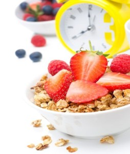 Granola with fresh berries for breakfast and yellow alarm clock
